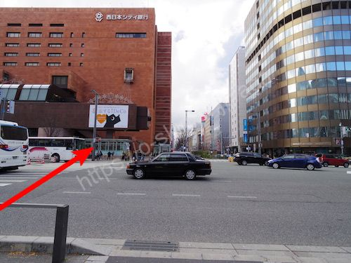 茶色いビルの目の前の信号を渡る