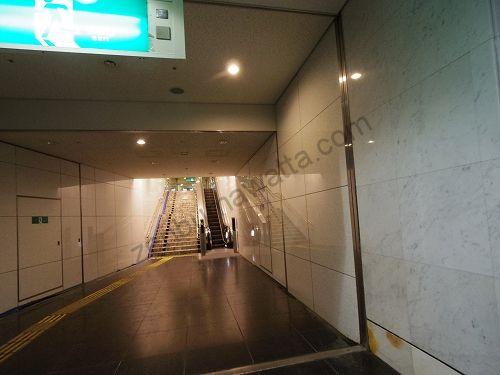 通路つきあたりにあるエスカレーター・階段で上に上がります